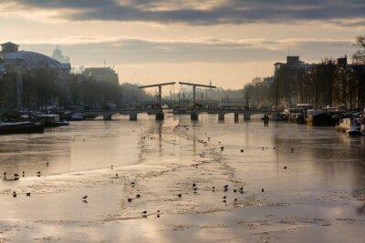 Vinilo Hermoso panorama de invierno del río Amstel en Amsterdam, Países Bajos, mirando hacia el Puente Delgado.