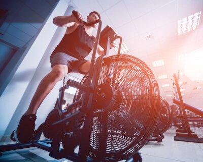 Vinilo Hombres jóvenes con cuerpo musculoso usando una bicicleta de aire para ejercicios cardiovasculares en un gimnasio de entrenamiento cruzado.