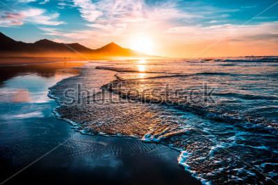Vinilo Impresionante puesta de sol y la playa con un horizonte infinito y figuras solitarias en la distancia e increíbles olas espumosas. Colinas volcánicas en el fondo.