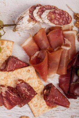 Vinilo Jamón, nueces, galletas y uva sobre fondo de madera blanca
