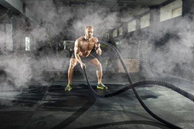 Vinilo Joven atlético con cuerda de batalla haciendo ejercicio en el gimnasio. Concepto deportivo