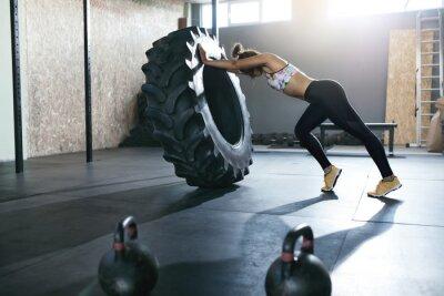 Vinilo Levantamiento de pesas. Deportista entrenando con rueda crossfit en el gimnasio