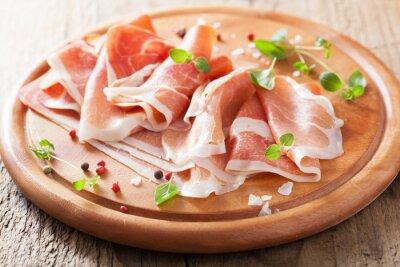 Vinilo lonchas de jamón prosciutto en cortar la placa con el orégano y la pimienta