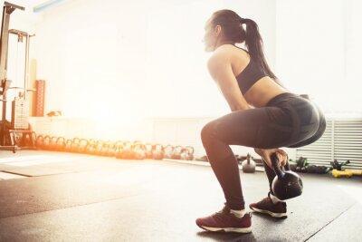 Vinilo Mujer atlética que ejercita con la campana de la caldera mientras que está en la posición de cuclillas. Mujer muscular que hace el entrenamiento del crossfit en el gimnasio.