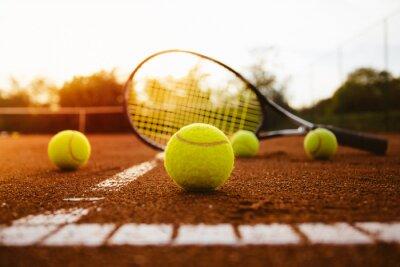Vinilo Pelotas de tenis con raqueta en la pista de tierra batida