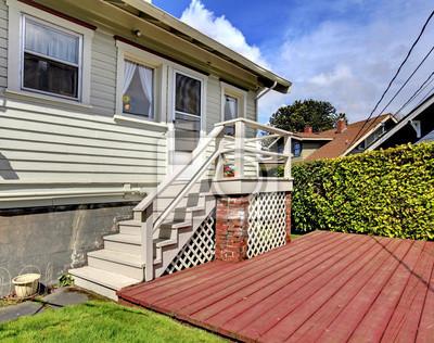 Pequeña casa gris con escalera hacia atrás cubierta de patio ...