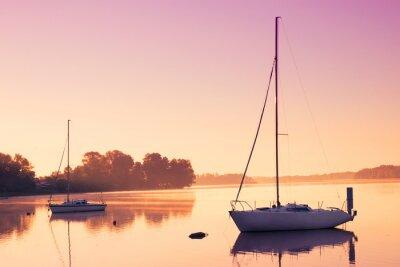 Vinilo Pequeños barcos de vela reflejan en el agua serena durante el amanecer.