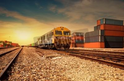 Vinilo Plataforma del tren de carga en la puesta del sol con el contenedor
