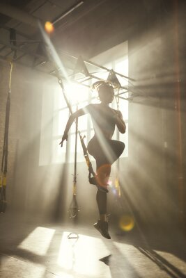Vinilo Professional training. Full-length of young athletic woman in sports clothing training legs with trx fitness straps in the gym.