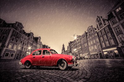 Vinilo Retro coche rojo en adoquín histórico casco antiguo en la lluvia. Wroclaw, Polonia.