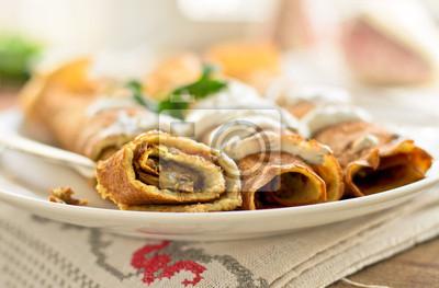 Rodillos de la crepe con setas y salsa de yogur