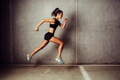 Vinilo Slim atractivo deportista corriendo contra un muro de hormigón