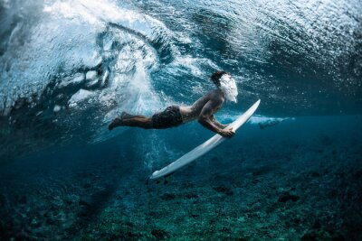 Vinilo Surfer performs dive (the duck dive) with his surfboard under the wave and exhales air into the water.