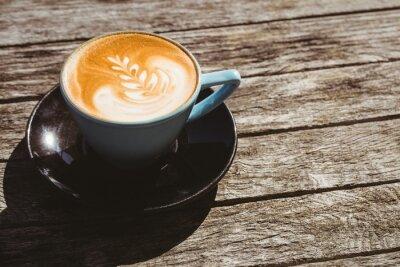 Vinilo Taza de cappuccino con café de arte en la mesa de madera
