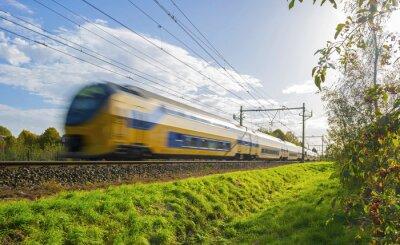 Vinilo Tren de pasajeros se mueve a gran velocidad en la luz del sol
