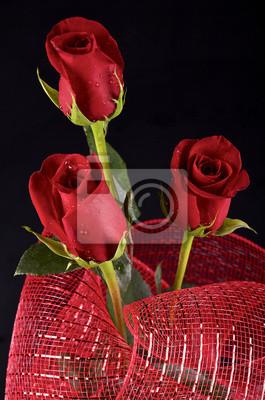 0aa60fcc0 Vinilo Tres rosas rojas y una cinta roja decorativa sobre fondo negro