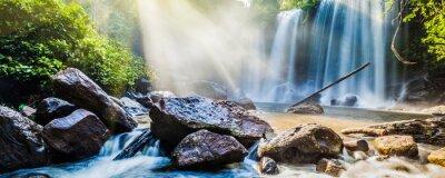 Vinilo Tropical cascada en la selva con los rayos del sol