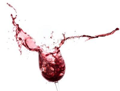 Vinilo Vino rojo que salpica fuera de un vidrio, aislado en blanco