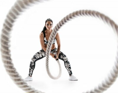 Vinilo Woman doing exercises with battle rope. Photo of muscular model in military sportswear isolated on white background. Strength and motivation