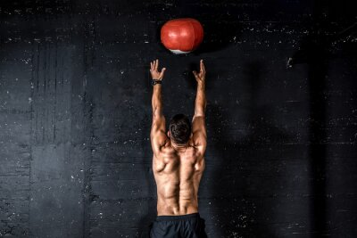 Vinilo Young strong sweaty focused fit muscular man with big muscles doing throwing medicine ball up on the wall for training hard core workout in the gym real people selective focus