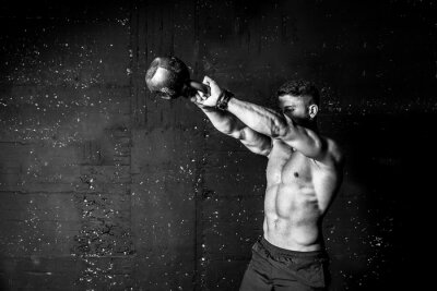 Vinilo Young strong sweaty focused fit muscular man with big muscles holding heavy kettle bell for swing cross training hard core workout in the gym black and white